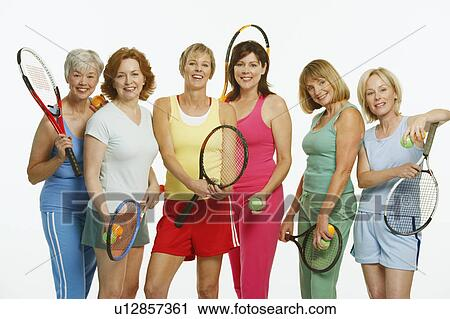Portrait of a group of mature women holding tennis rackets and tennis balls  Stock Image   u12857361   Fotosearch