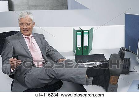 Banque de photo homme à pieds bureau u recherchez