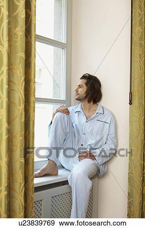 Stock Fotograf Junger Mann Sitzen Auf Fensterbank Tragen