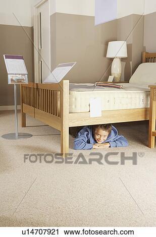 Stock Fotografie Junge Verstecken Unter Bett In Mobel Store