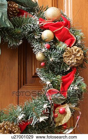 Detail Of Christmas Wreath With Evergreen Garland Rred Gold Ribbons Gold Balls Pine Cones And Red Berry Decorations On Light Brown Wooden Door