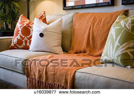 Comfortable Sofa With Orange Throw Blanket And Decorative Pillows Stock Photo