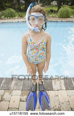 Girl in snorkeling gear standing at edge of swimming pool Stock Photography