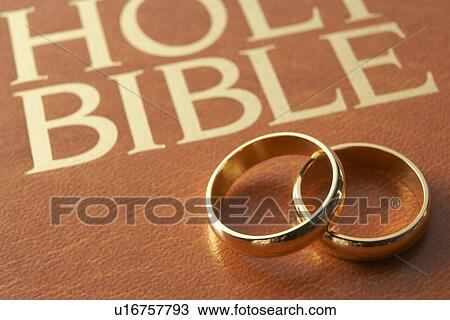 stock photo of wedding rings resting on a holy bible u16757793