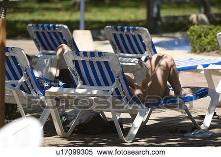Enjoyable Tropical Resort Swimming Pool With Blue And White Striped Sun Tanning Beach Chairs Bed People Lounging And Reading Relaxing On Vacation Stock Caraccident5 Cool Chair Designs And Ideas Caraccident5Info