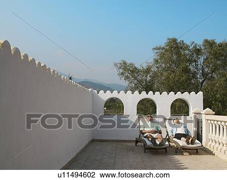 Stock photo of senior couple sunbathing on balcony terrace for Balcony sunbathing