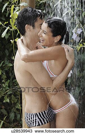 Young Couple Hugging Under Shower Near Plants Stock Photo