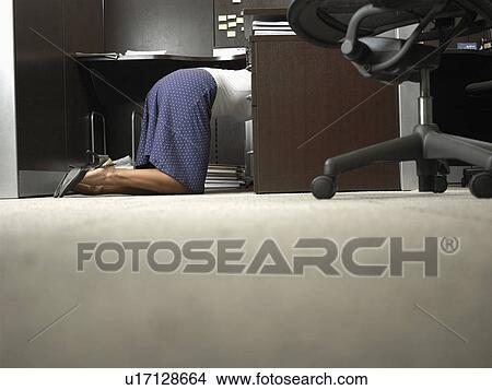 Stock photo of female office worker kneeling under desk u
