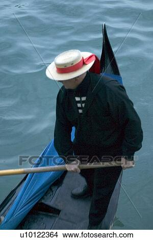 Stock Photo of Gondolier with red ribbon straw hat on stern of ... 1afd006b6
