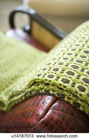 Stock Photo Of Green And Brown Throw Blanket On Leather