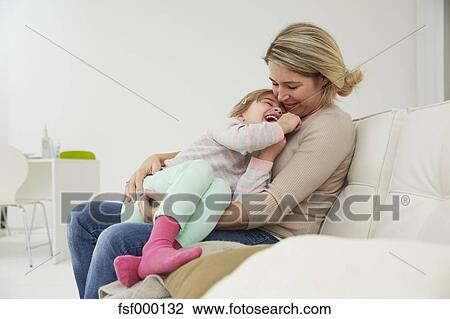 Etonnant Germany, Munich, Mother And Daughter Sitting On Sofa, Cuddling