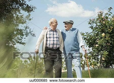 stock image of two old friends walking in the park uuf000685