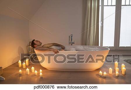 9d32a5f5ba Archivio fotografico - uomo rilassa, in, vasca bagno, con, illuminato,  candele