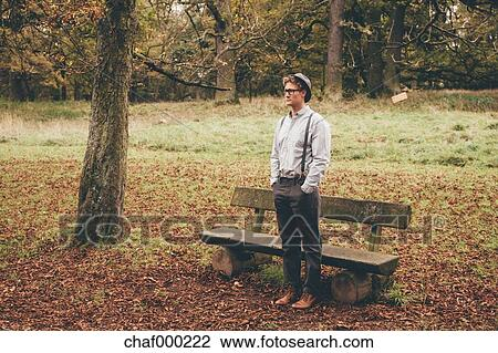 Stock Photo Of Young Man Standing In Front Of A Bench In Autumnal