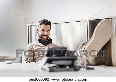 Banque de photo homme dans bureau pose sien pieds bureau