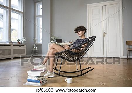 Peachy Young Woman Sitting On Rocking Chair At Home Reading A Book Pdpeps Interior Chair Design Pdpepsorg