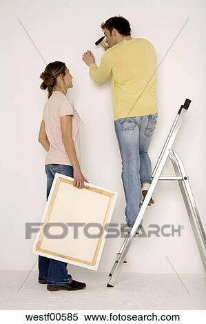 Stock Image Young Hanging Up Painting Man Standing On Ladder Fotosearch