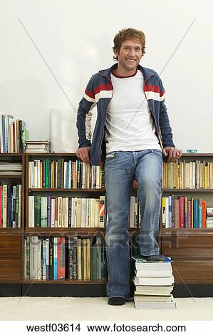 Stock Photo Of Young Man Standing In Front Bookshelf Feet On